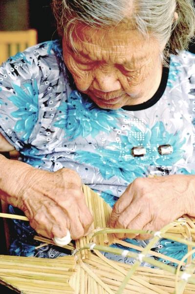 编制当地有名的手工艺品——稻草鱼.-农耕继世久 稻鱼染金秋
